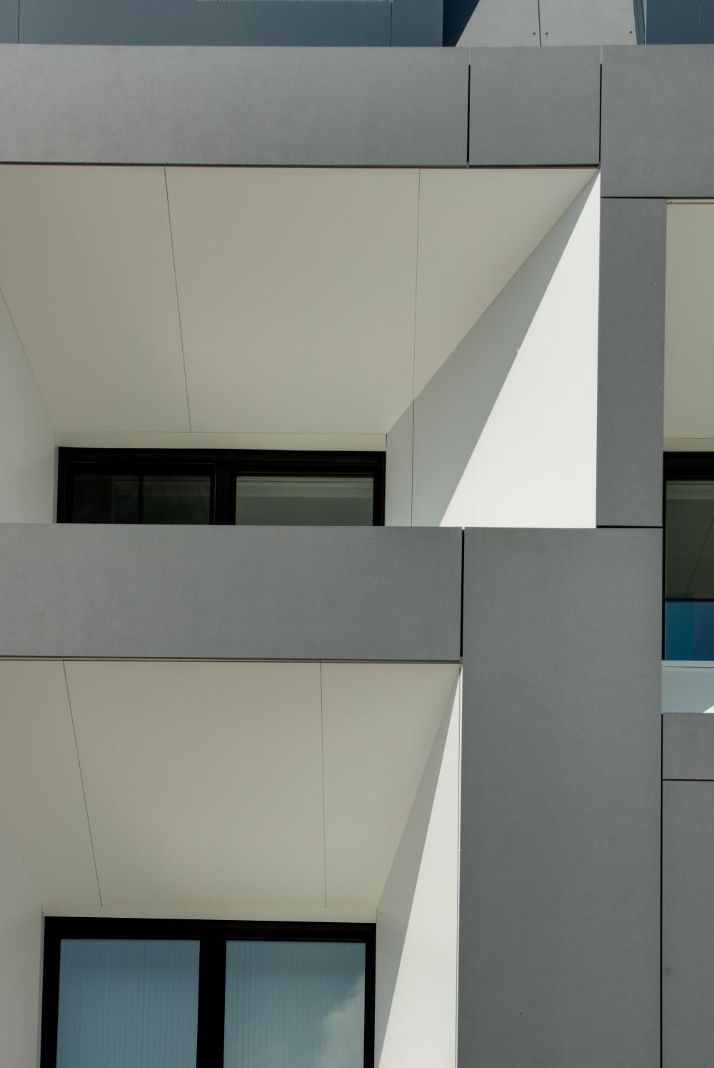 Abscis Architecten - Het daglicht weerkaatst op de witte glanzende aluminiumpanelen - fotografie Inge Claessens